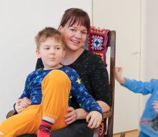 Teija Rautio iloitsee vertaistuesta, jota Perheentalossa on tarjolla. Äidin sylissä istuu Daniel-poika ja vauhtia antaa pikkuveli Oliver.