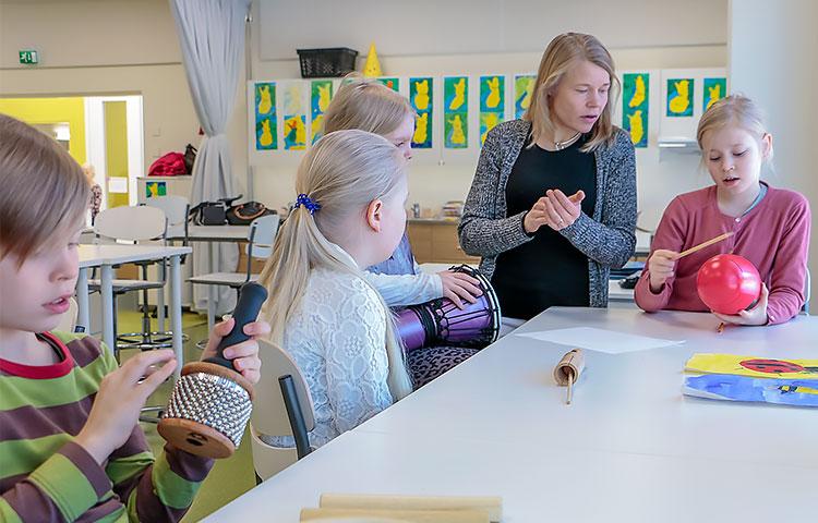 Erityisluokanopettaja Vuokko Palokangas pohtii yhdessä oppilaiden kanssa rytmien maailmaa.