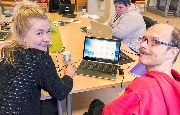 Janne Tavast (oikealla) valikoi viestintäryhmässä kuvia ja tekee haastatteluja. Tukihenkilönä on Liisa Toiviainen.