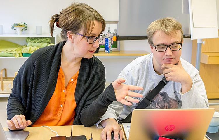 Teemu Kumpu on erikoistunut viestintäryhmässä kirjoittamiseen. PäheeOTE:n projektisuunnittelija Elina Huttunen ohjaa Kumpua PowerPoint-esityksen tekemisessä.