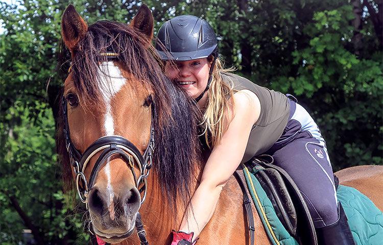 Nuori nainen ratsastaa hevosella.