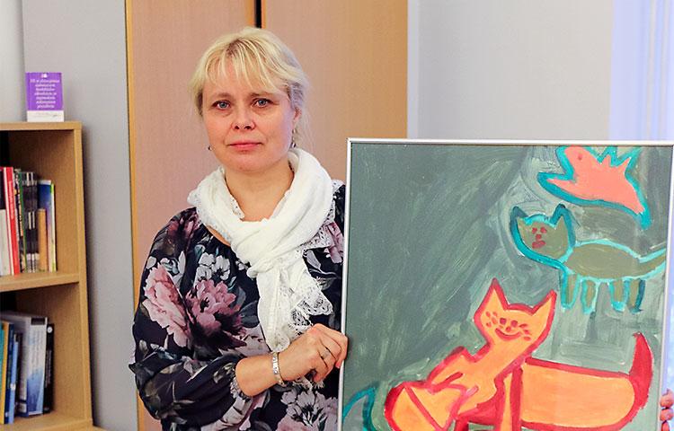 Anna-Elina Leskelä-Rannan työhuoneen seinää koristaa kehitysvammaisen taiteilijan värikylläinen teos, josta välittyy positiivinen tunnelma.