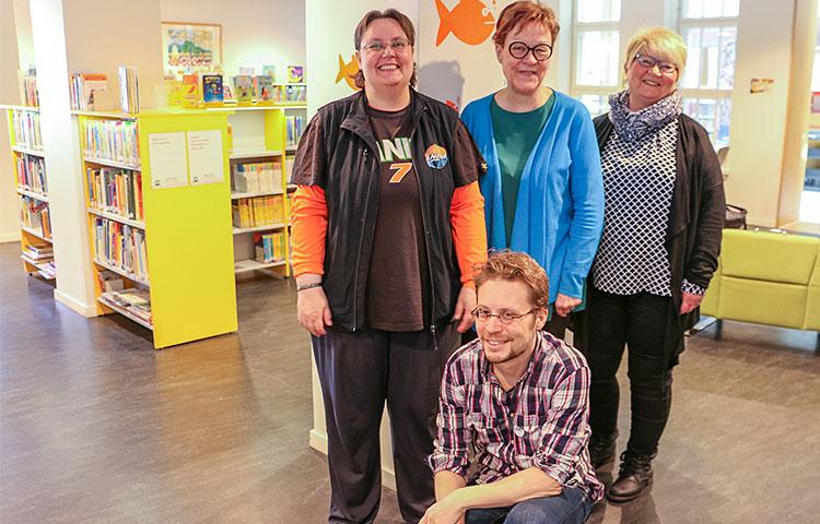 Neljä ihmistä kirjastossa.