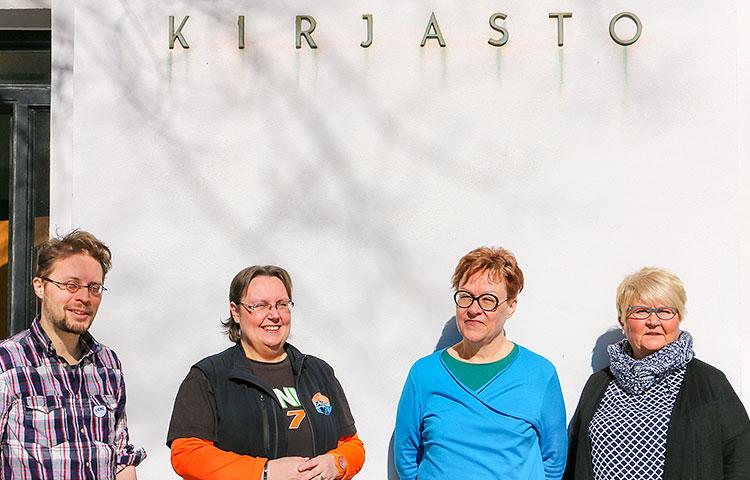 Kolme naista ja yksi mies seisovat kirjaston edustalla.