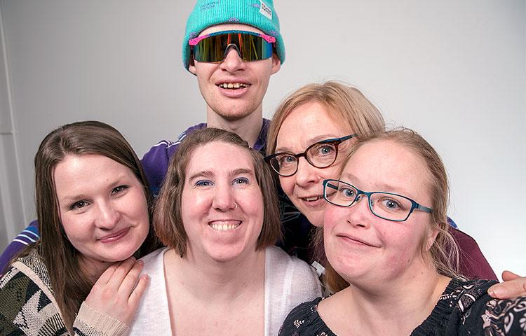 Viisi hymyilevää ihmistä on kokoontunut ryhmäkuvaan.