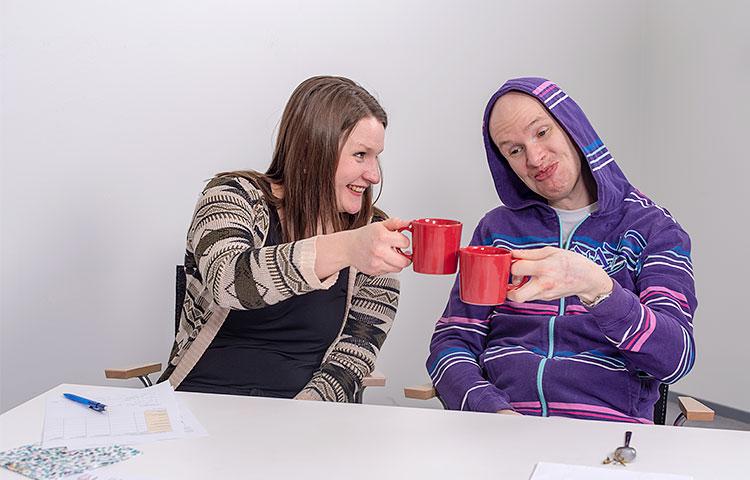 Nainen ja mies istuvat hymyillen pöydän ääressä. Molemmilla on kädessä kahvikuppi.