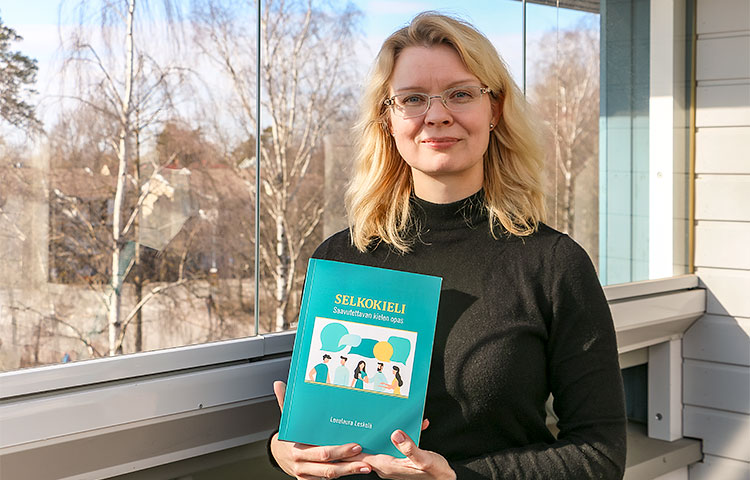 Leealaura Leskelä pitelee käsissään Selkokieli - Saavutettavan kielen opas -teosta.