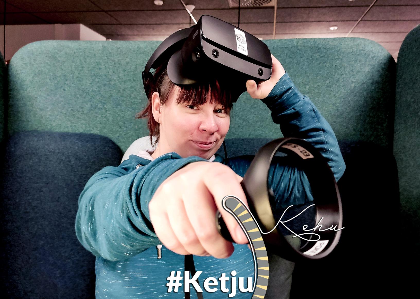 Kuvassa Katja Huttunen VR-lasit ohjallaan katsoo kameraan ja osoittaa ohjaimella sitä kohti.