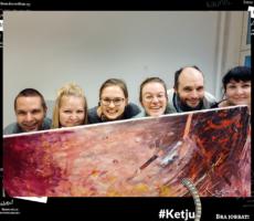 Kuvassa Wärjäämön porukka kurkistelee upean maalatun taideteoksen takaa.