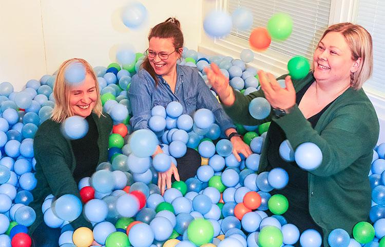 Kolme naista leikkii pallomeressä.