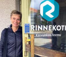Hymyilevä nainen seisoo oven edustalla.