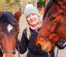 Lähikuva nuoresta naisesta ja kahdesta hevosesta.