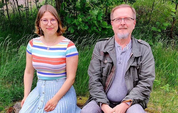 Nainen ja mies istuvat ulkona.