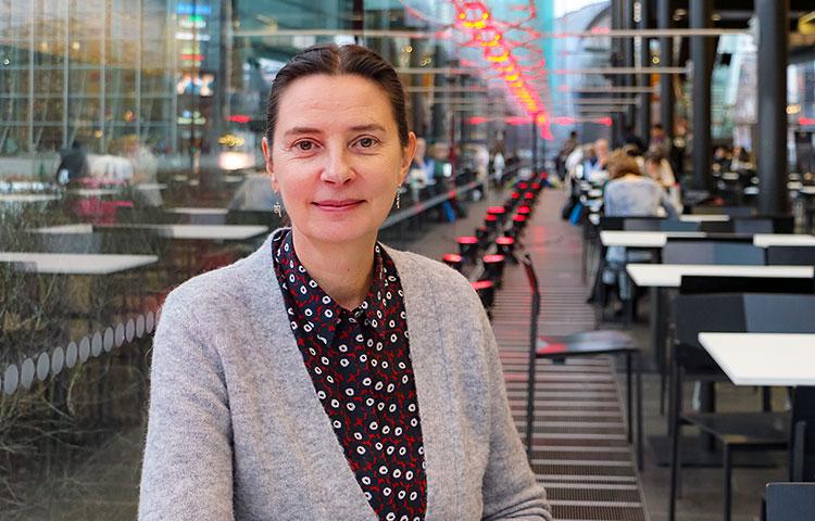 Anne Brunila istuu ravintolasalissa.