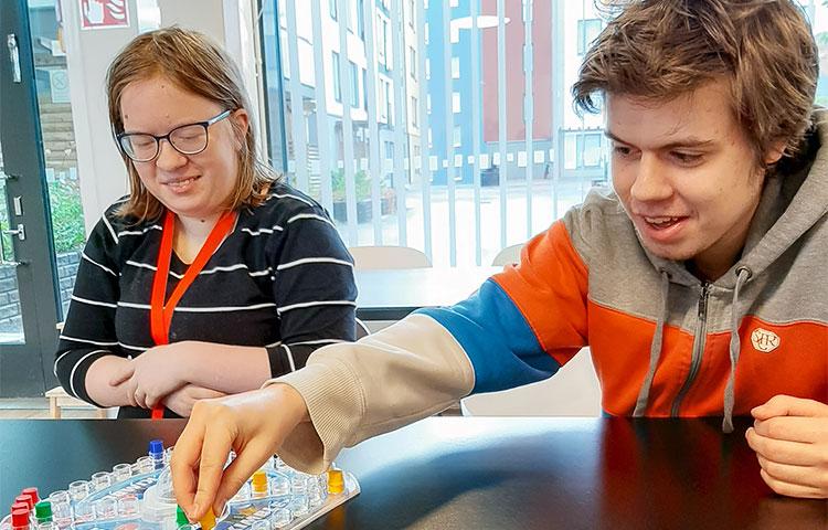 Nuori nainen ja nuori mies pelaavat lautapeliä.