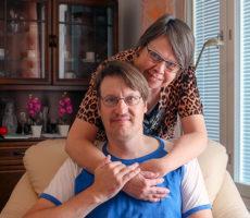 Nainen on kietonut kätensä sohvalla istuvan miehen hartioille.