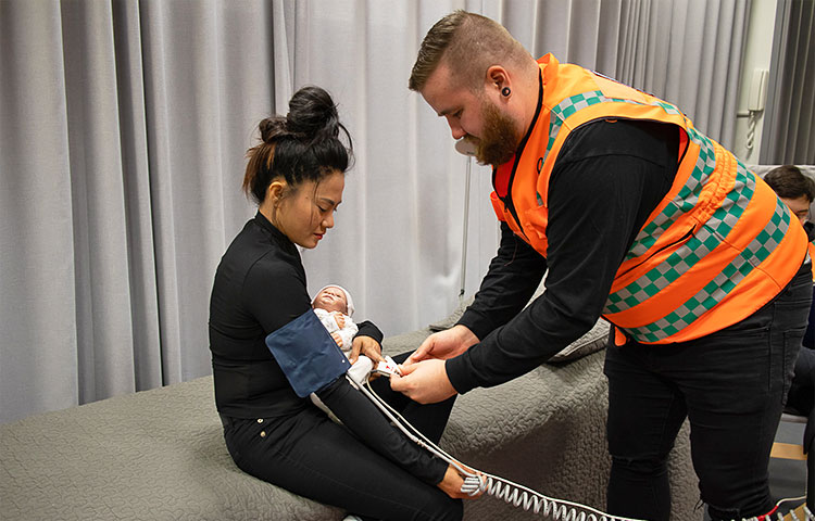 Mies auttaa istuvaa naista.