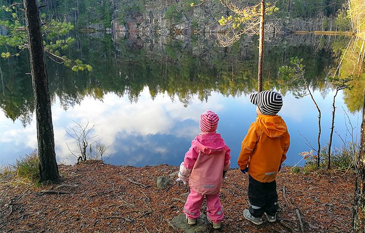 Kaksi lasta järven rannalla.