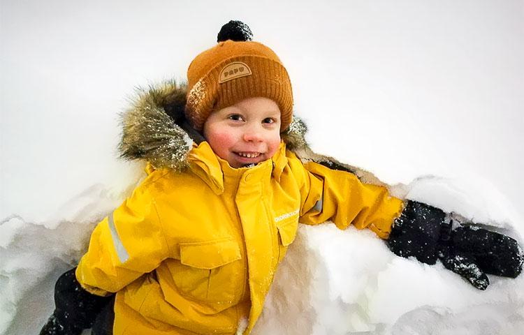 Poika leikkii lumihangessa.