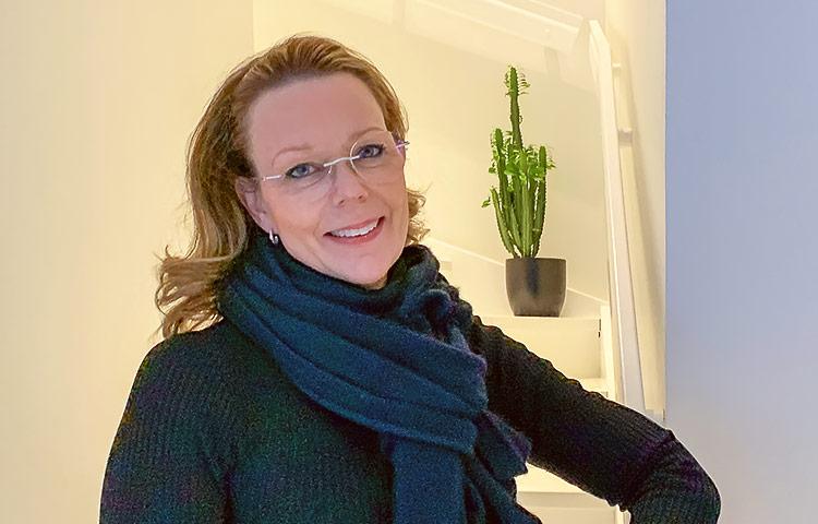 Lähikuva hymyilevästä naisesta, taustalla portaat.
