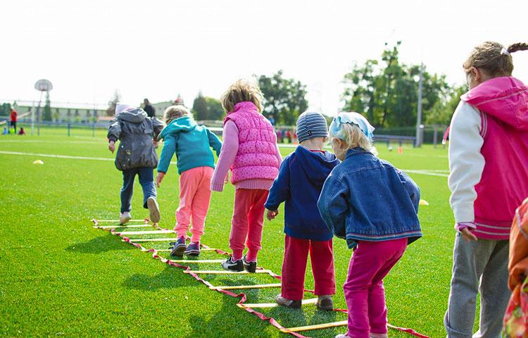 Lapsia leikkimässä urheilukentällä.