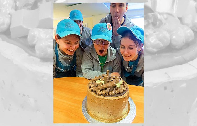 Viisi ihmistä kakun ääressä.