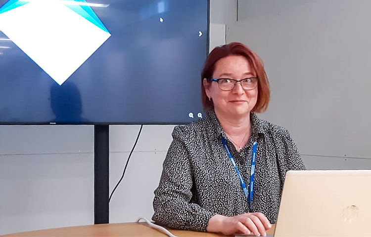 Nainen työpöydän ääressä, edessä kannettava tietokone.