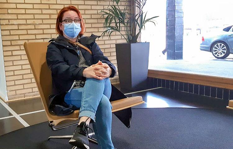 Nainen istuu, kasvoilla on sininen maski.