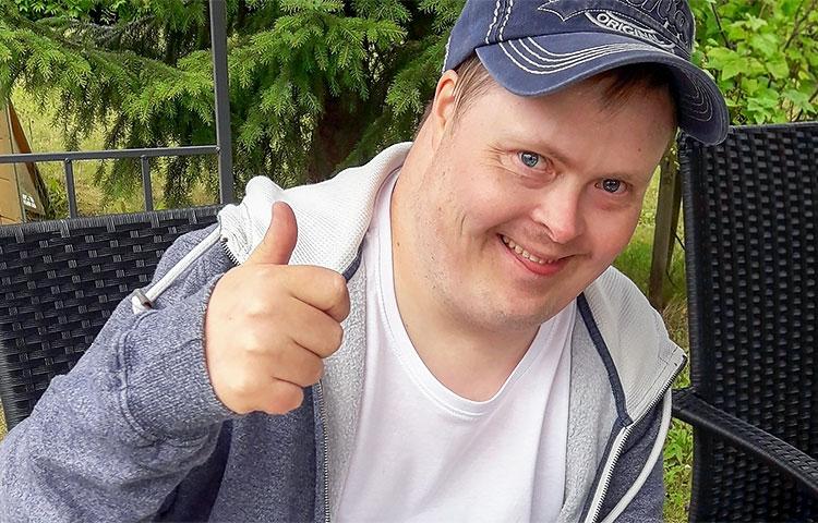 Mies hymyilee peukku pystyssä.