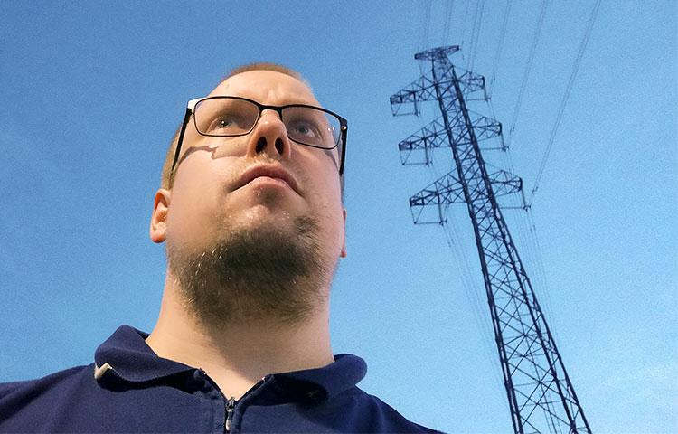 Lähikuva miehestä, taustalla sähkölinja.