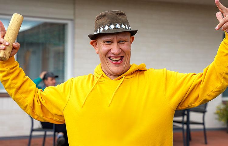 Keltaiseen huppariin pukeutunut mies hymyilee leveästi.