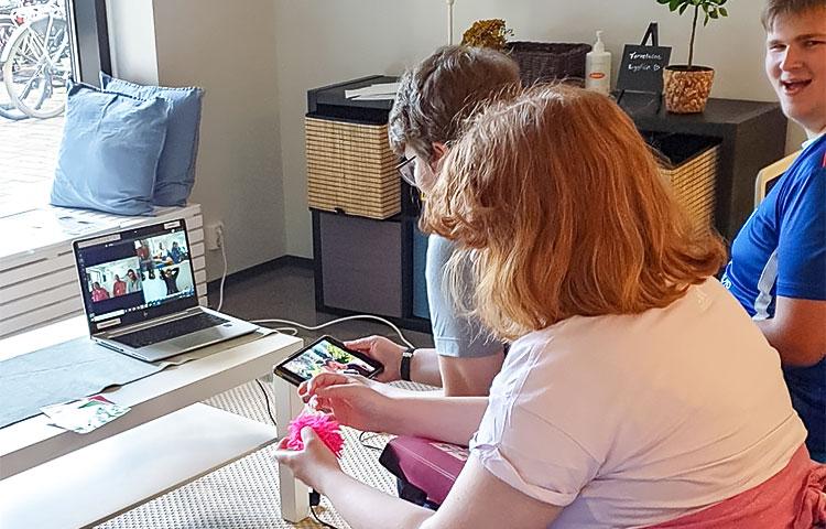 Kolme ihmistä käyttää kannettavaa tietokonetta ja tablettia.